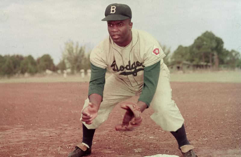 American professional baseball player Jackie Robinson (1919 - 1972) of the Brooklyn Dodgers, dressed in a road uniform, crouches by the base and prepares to catch a ball, 1951.