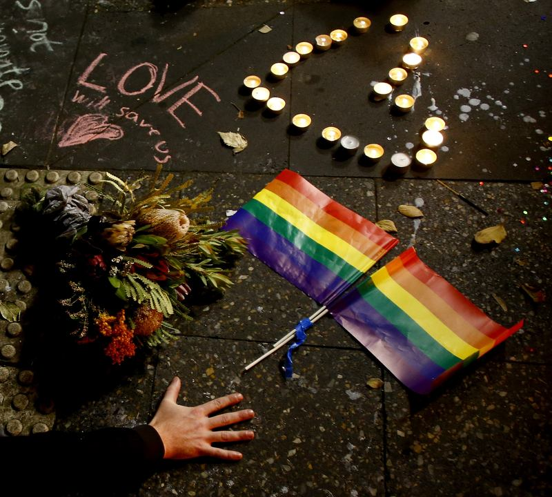 A man touches the ground next to rainbow flags during a candlelight vigil for the victims of the Pulse Nightclub shooting in Orlando, Florida on June 13, 2016 in Sydney, Australia.