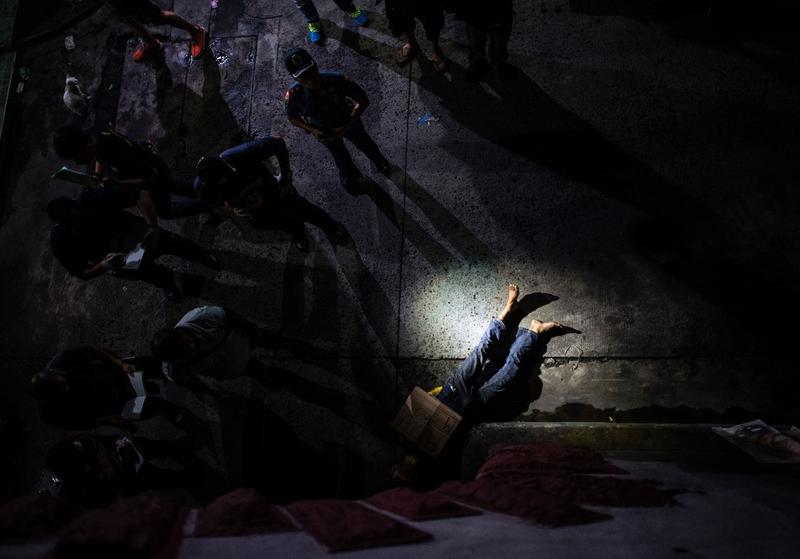July 8, 2016: Police officers investigate the dead body of an alleged drug dealer, his face covered with packing tape and a placard reading 'I'm a pusher,' in Manila.