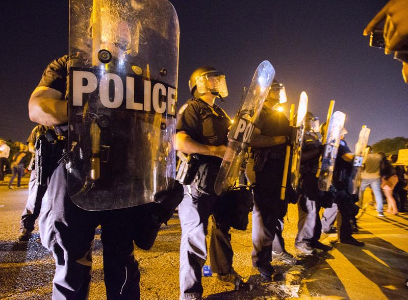 Protesters face off with Baton Rouge police in riot gear across the street from the police department on July 8, 2016 in Baton Rouge, Louisiana.