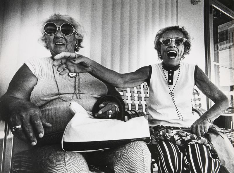 Miami, Florida: Anna Kronenfeld and Sadye Weiss share a joke on the porch in front of the George Washington Hotel on Collins Avenue. 1975