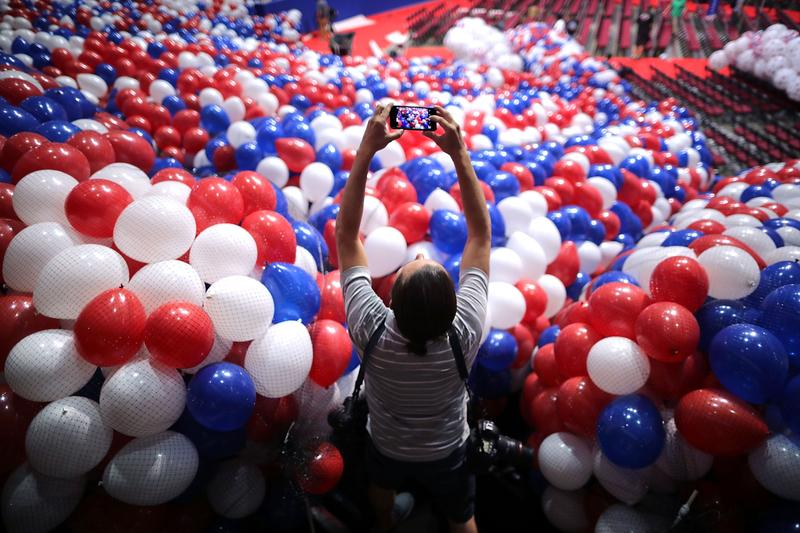 A news photographer makes images of nets filled with thousands of red, white and blue balloons before they are lifted into the ceiling of the Quicken Loans Arena July 15, 2016 in Cleveland, Ohio.