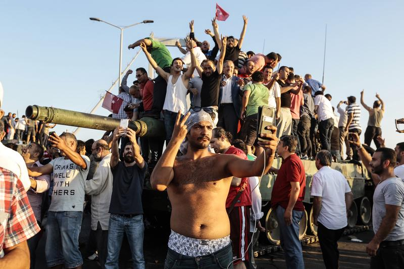 Supporters of Turkish President Recep Tayyip Erdogan wave flags as they capture anTurkish Army APC after soldiers involved in the coup surrendered on Bosphorus bridge on July 16, 2016 in Istanbul.