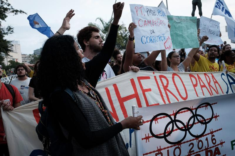 Protesters hold banners against Rio 2016 Olympic games to demand more education or health care during a demonstration against the Olympic torch relay in Niteroi, on August 2, 2016.