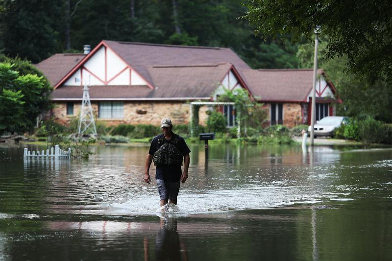 Ryan Evans walks along a flooded road on August 15, 2016 in Baton Rouge, Louisiana.