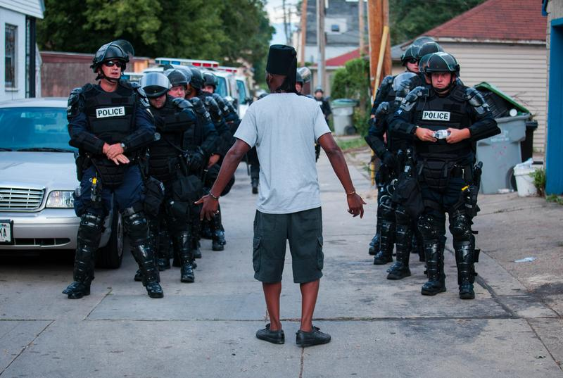 A man talks to police in riot gear as they wait in an alley after a second night of clashes between protestors and police August 15, 2016 in Milwaukee, Wisconsin.