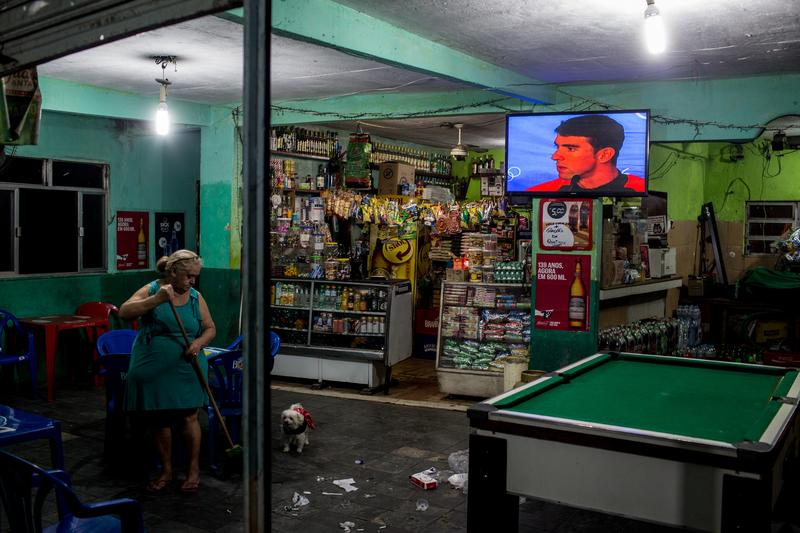 A woman cleans her shop as the Olympic games are seen on a tv screen in the Vidigal 'favela' community on August 14, 2016 in Rio de Janeiro, Brazil.