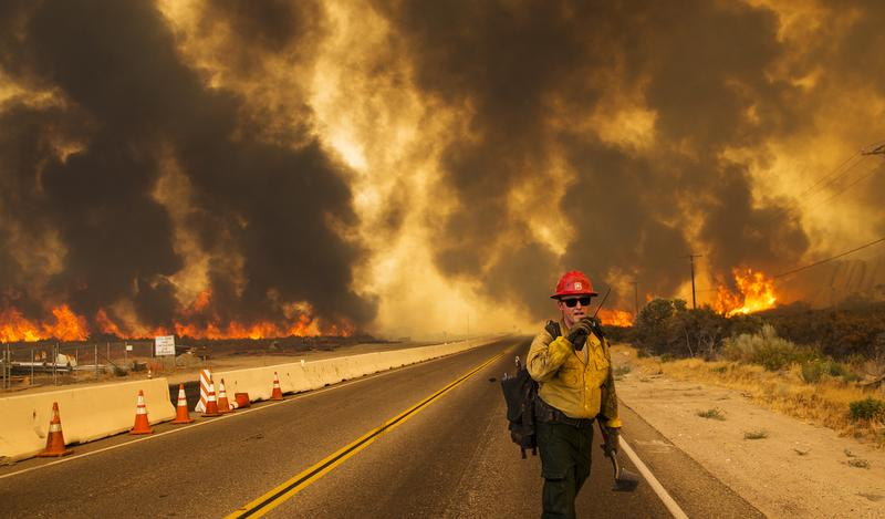A firefighter radios that the Blue Cut Fire is burning on both sides of Highway 138 on August 16, 2016 in Phelan, California.