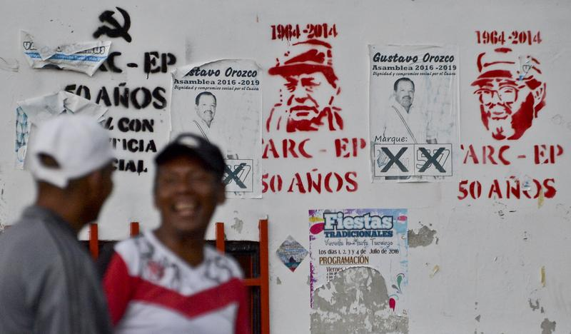 Men in Colombia stand in front of FARC ceasfire graffiti.