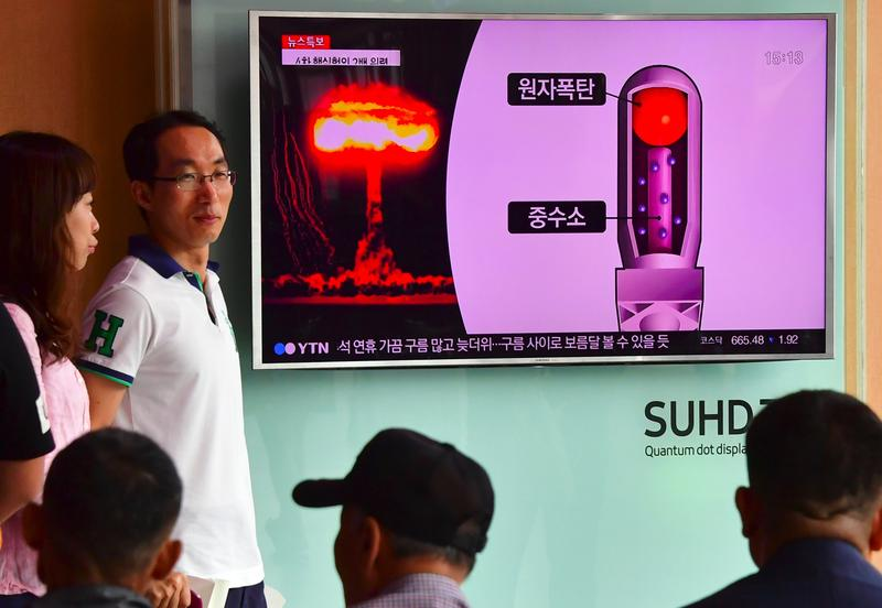 People watch a television news report on North Korea's latest nuclear test at a railway station in Seoul on September 9, 2016.
