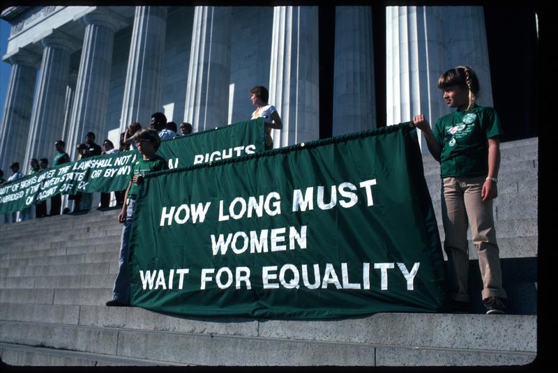 Young girls hold up banners supporting women's equality at the 'Call to the Nation's Conscience' ERA rally on the steps of the Lincoln Memorial October 12, 1981 in Washington, DC.