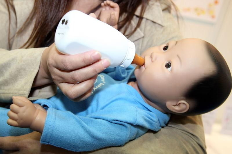 A woman holds the child-care simulation robot 'My Baby 2' by Realityworks during the 2007 International Robot Exhibition at Tokyo Big Site on November 28, 2007 in Tokyo, Japan.