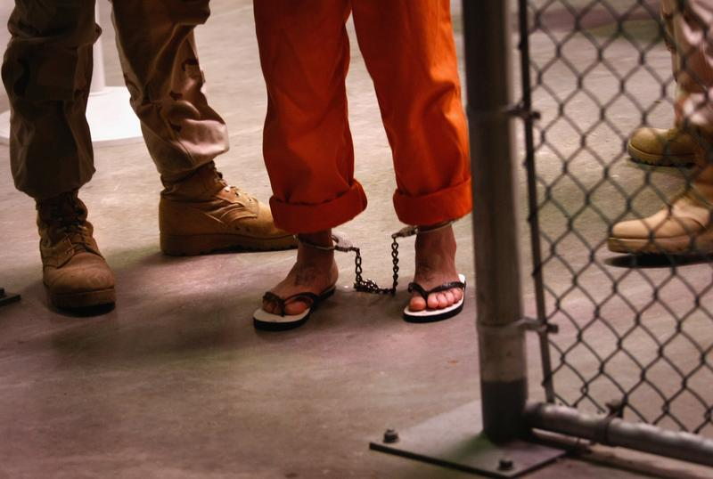 A 'non-compliant' detainee is escorted by guards after showering inside the U.S. military prison for 'enemy combatants' on October 27, 2009 in Guantanamo Bay, Cuba.