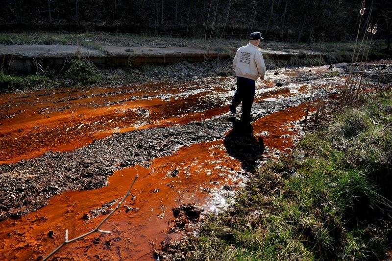 Larry Gibson (pictured) walks past leeching orange colored water (has sulfuric acid in it among other waste) that's flowing downhill near Kayford, West Va.