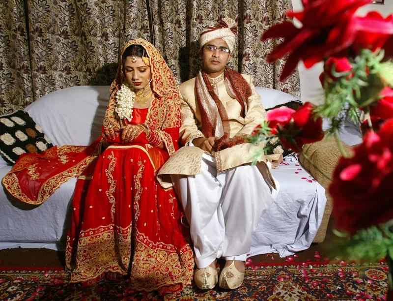 Asim Bukhari nervously sits close to his wife Nida, having just returned from their wedding ceremony, Aug. 18, 2003. Asim returned to his family in Pakistan where they have arranged his marriage.