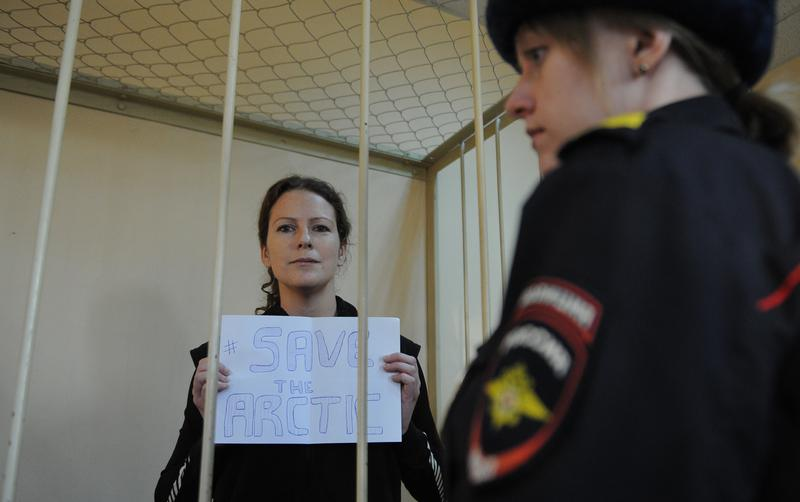 Greenpeace International activist, one of the 'Arctic 30,' Ana Paula Alminhana Maciel from Brazil, holds a poster in a defendant cage in a court in Saint Petersburg, Russia, November 18, 2013.