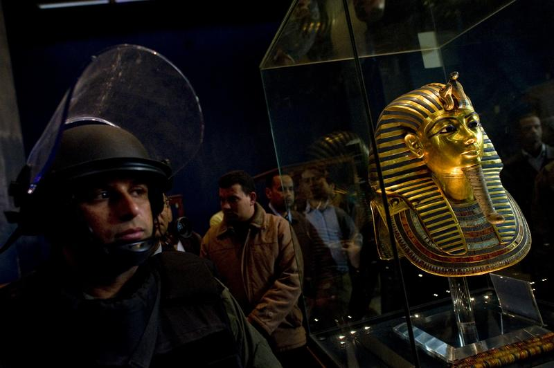 A soldier stands guard next to Tutankhamun's gold funerary mask inside the Egyptian Museum as Egyptian state minister of antiquities Zahi Hawass talks to reporters on February 16, 2011