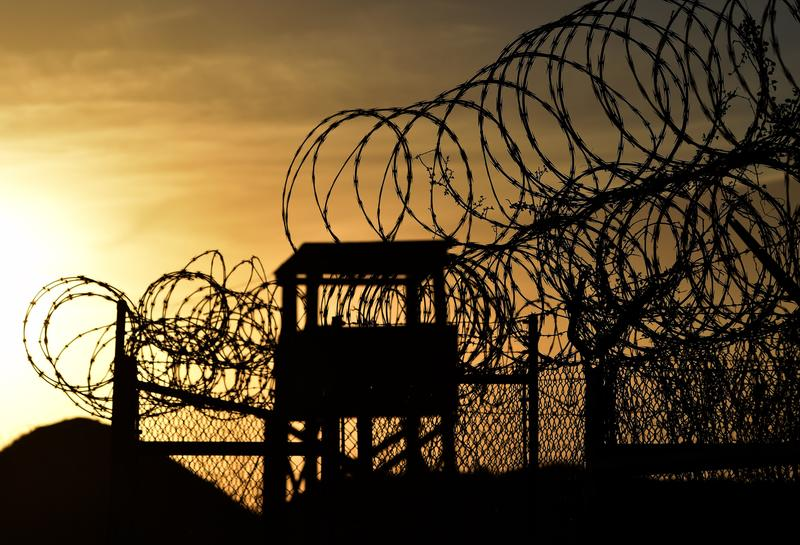 Razor wire-topped fence and a watch tower at the abandoned 'Camp X-Ray' detention facility at the US Naval Station in Guantanamo Bay, Cuba, April 9, 2014.