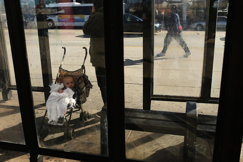 A child and mother wait for a bus on October 11, 2012 in Camden, NJ. According to the U.S. Census Bureau, Camden is the most impoverished city in the United States.