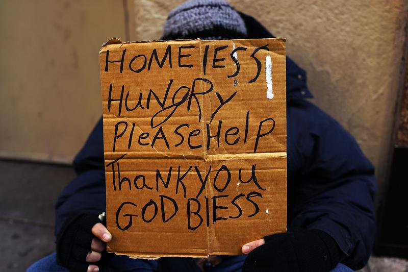 A person in economic difficulty holds a homemade sign asking for money along a Manhattan street on December 4, 2013 in New York City.