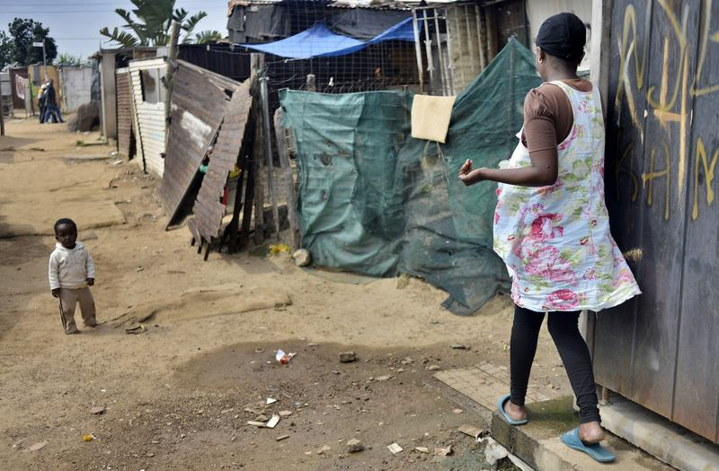 A woman walk in a dusty alley in the impoverished Diepsloot township outside Johannesburg on April 16, 2014.