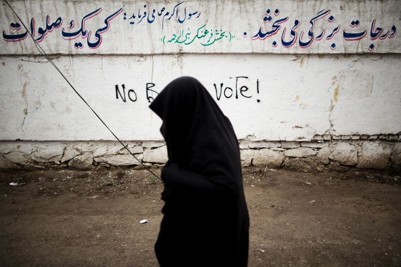 An Afghan resident walks past a graffiti slogan against the presidential election in the city of Herat on April 3, 2014. Afghans vote on April 5 for a successor to Hamid Karzai.