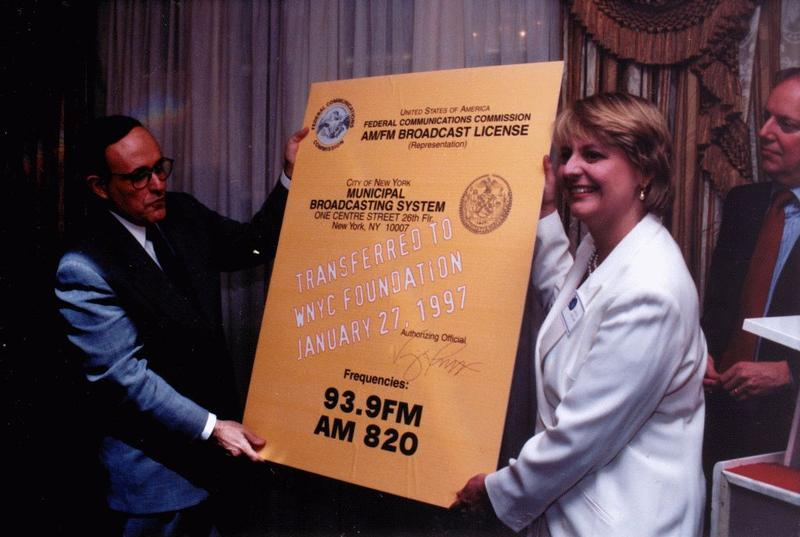 January 27, 1997, Mayor Giuliani hands WNYC CEO Laura Walker a copy of the official FCC Broadcast License, signifying the station's transfer to the WNYC Foundation.