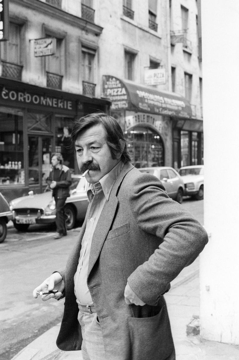 German poet, novelist, playwright, and graphic artist Gunter Grass smokes a cigarette  on a city street corner in March 1979.