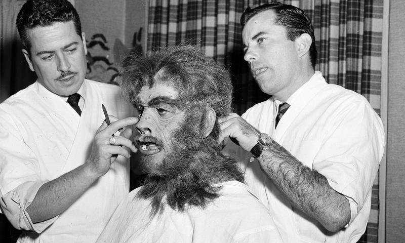 """Make-up artists fasten the """"Mr. Hyde"""" mask on actor Boris Karloff for """"Abbott and Costello Meet Dr. Jekyll and Mr. Hyde"""""""
