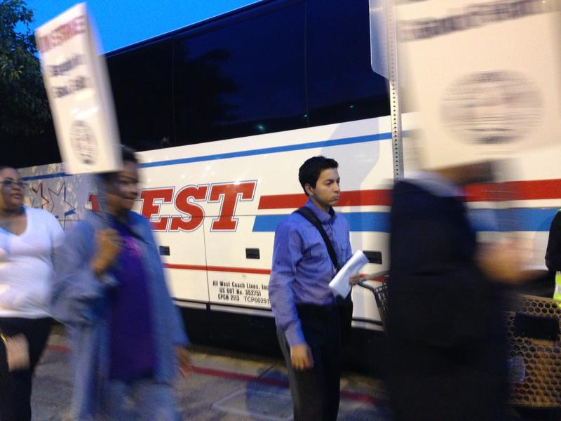 BART workers walking in a picket line as a commuter waits for a charter bus during the July strike. BART plans to raise the number of buses it charters if there's another strike.