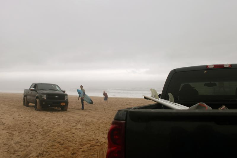 Trucks full of surfers and surfboards pull up on the town beach at Montauk on the Friday before Memorial Day. The surf was pounding and despite the fog and light drizzle, the beach was crowded.