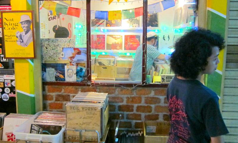 Samson Pho (behind windows) looks through the inventory in his shop, Laid Back Blues Records.