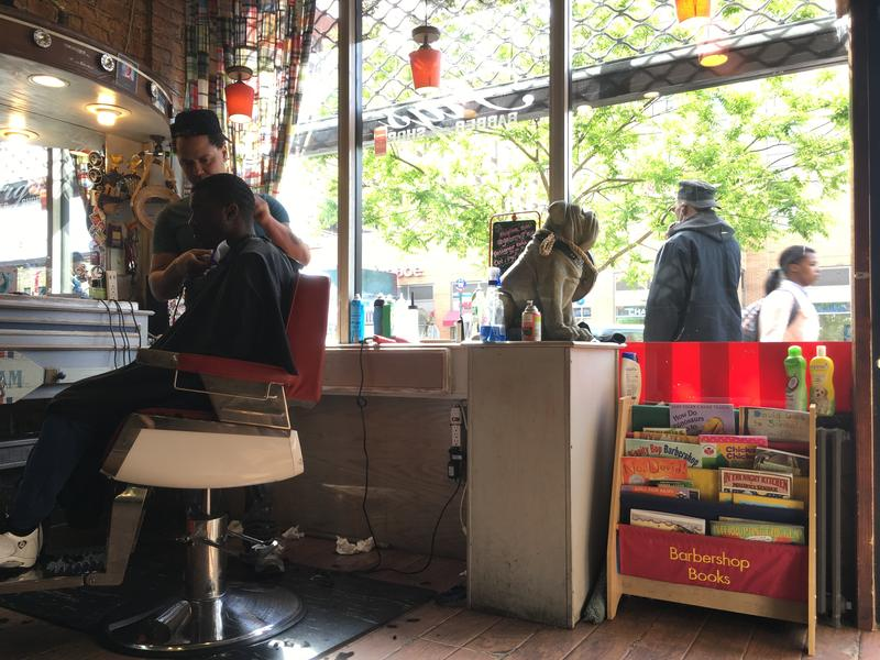 "A ""Barbershop Books"" shelf sits near the doorway of Fig's Barbershop on Frederick Douglass Boulevard in Harlem."