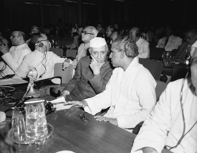 Indian Prime Minister Jawaharlal Nehru, left, tucks his chin in his hand as he confers with V. K. Krishna Menon of the Indian delegation at the Bandung Conference on April 24, 1955.