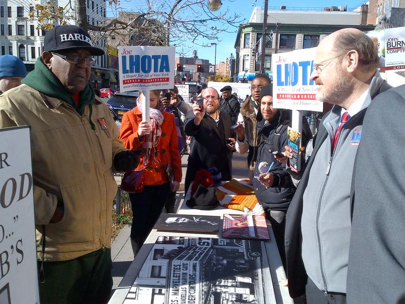 Republican mayoral candidate Joe Lhota talks with street vendor and artist Kelvin Maull on W.125th Street the day before Election Day.