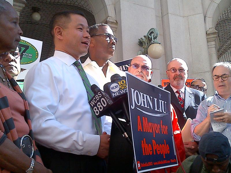 John Liu surrounded by supporters vows to continue his 2013 mayoral campaign despite the Campaign Finance Board's decision to deny matching funds.