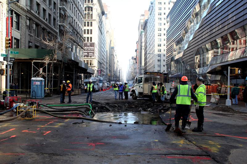 A water main break early on January 15, 2013 leaves a crater in the street at 13th Street and 5th Avenue.