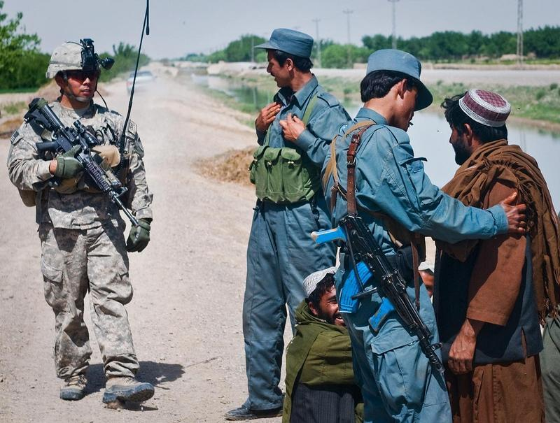 Afghan National Policemen and a U.S. Army Soldier from 3rd Platoon, Mad Dog Troop, 4th Squadron, 2nd Stryker Cavalry Regiment, interact with villagers while on patrol near Kandahar Airfield.