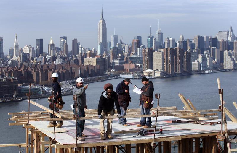 In this Nov. 12, 2008 file photo, carpenters work on the roof of a 30-story condominium project in the Williamsburg section of New York.