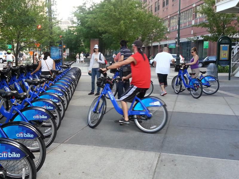 Citi Bike riders wait to return bikes at a full docking station.