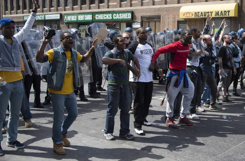 Demonstrators standing in front of a police line call for peace after a bottle was thrown at them on W. North Avenue in Baltimore, Maryland, April 28, 2015.