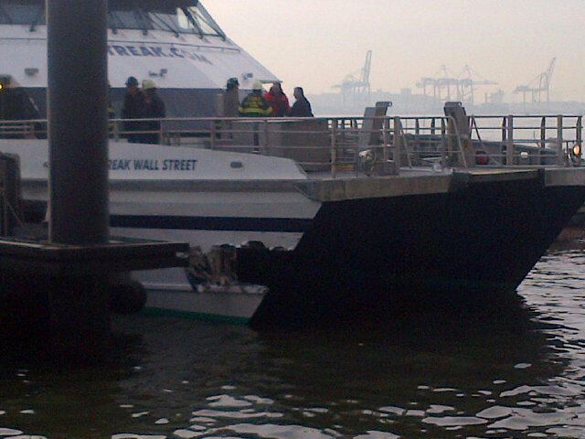 The hull of the Seastreak Wall Street catamaran ferry is visibly damaged after a docking accident.