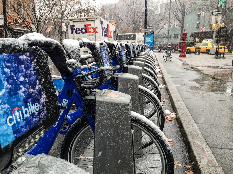 A Citi Bike docking station covered in wet snow.