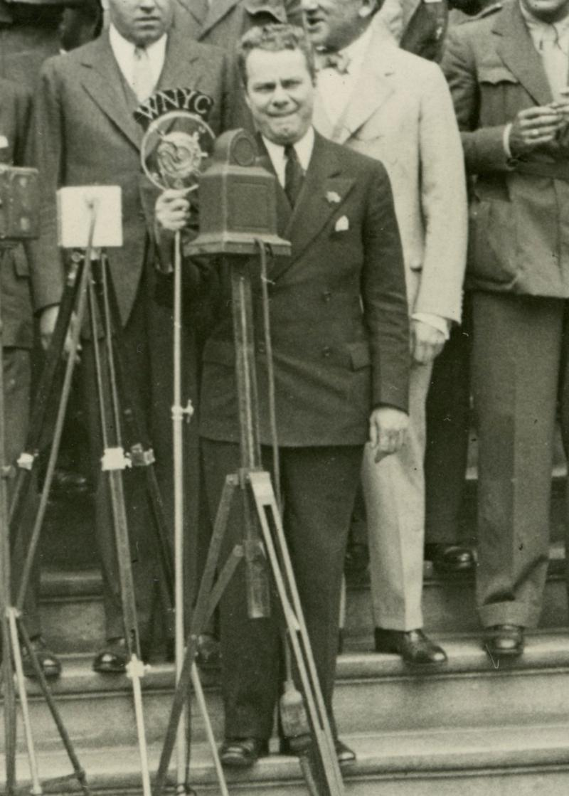 WNYC Announcer Tommy Cowan on the steps of City Hall with the WNYC mic in 1932.