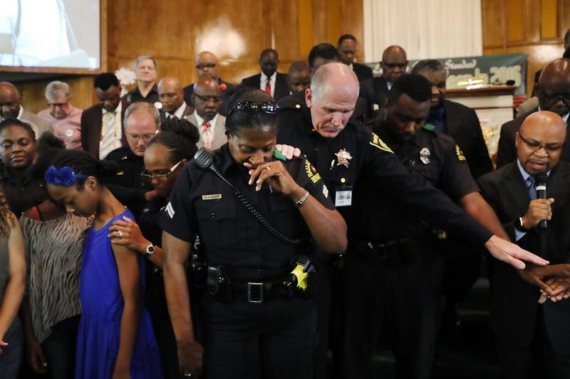 Police officers from area departments in and around Dallas pray at a multicurtural prayer vigil on July 10, 2016 in Dallas, Texas.