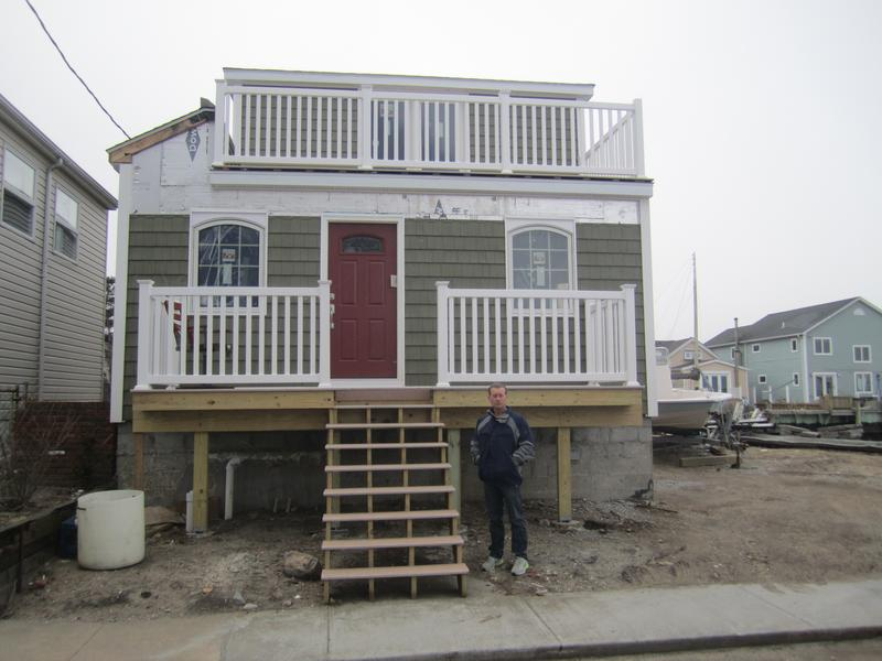 Dan Mundy, president of the Broad Channel Civic Association, in front of house that has been elevated, but not enough to satisfy FEMA's advisory flood maps.
