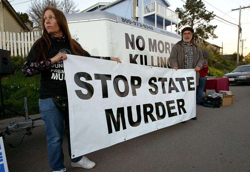 Melanie Bostic (L) of Lancaster, California and Michael Wharton of San Leandro, California hold a sign outside of the California State Prison at San Quentin February 9, 2004 in San Quentin, California