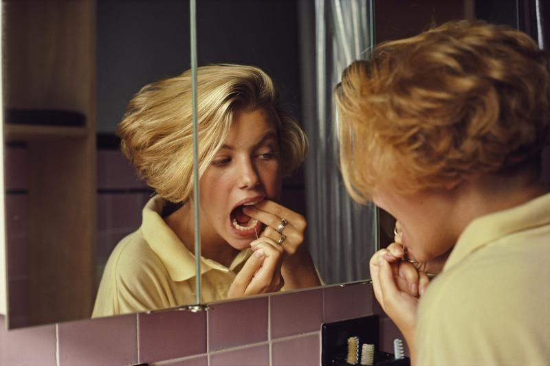 A young woman flossing her teeth in the bathroom mirror, USA, September 1985.
