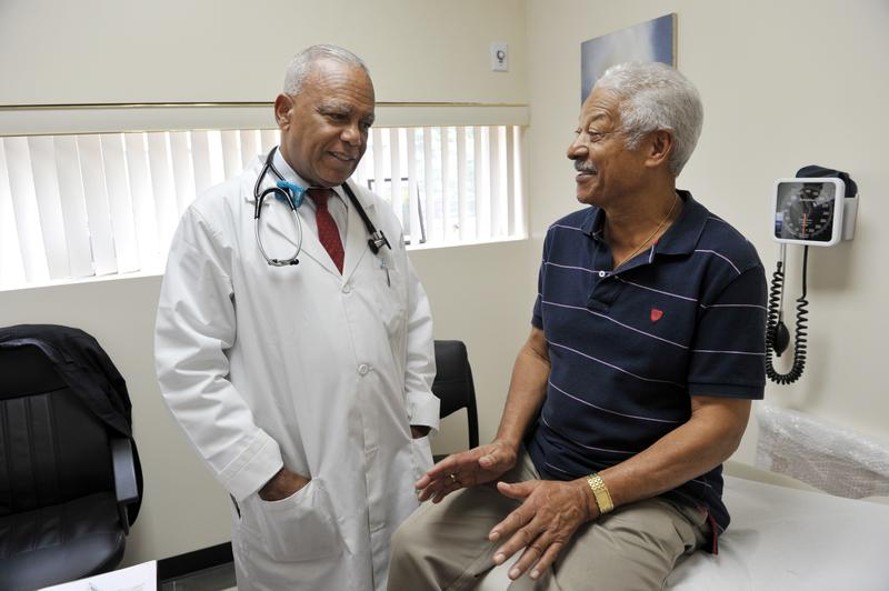 Dr. Sixto Caro speaks with patient Jose Rodriguez at the Medspan Associates clinic in New York.