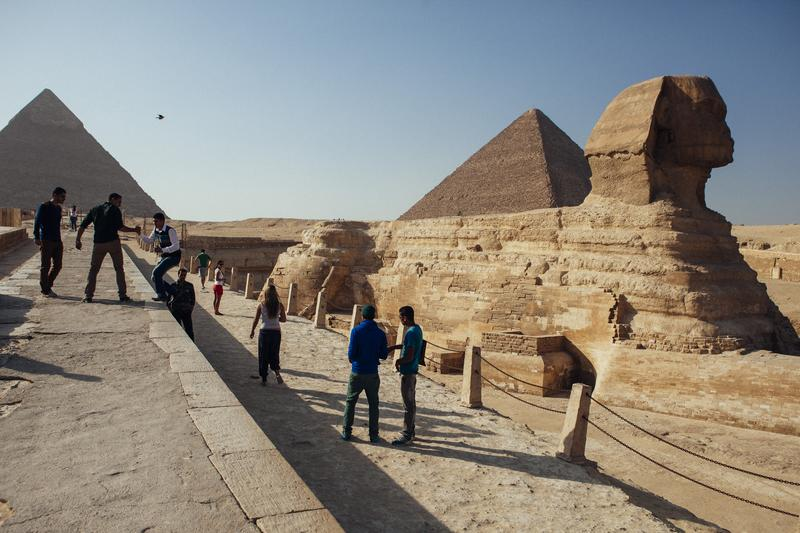A group of tourists pose for photographs in front of the Sphinx at the Pyramids of Giza in Cairo, Egypt